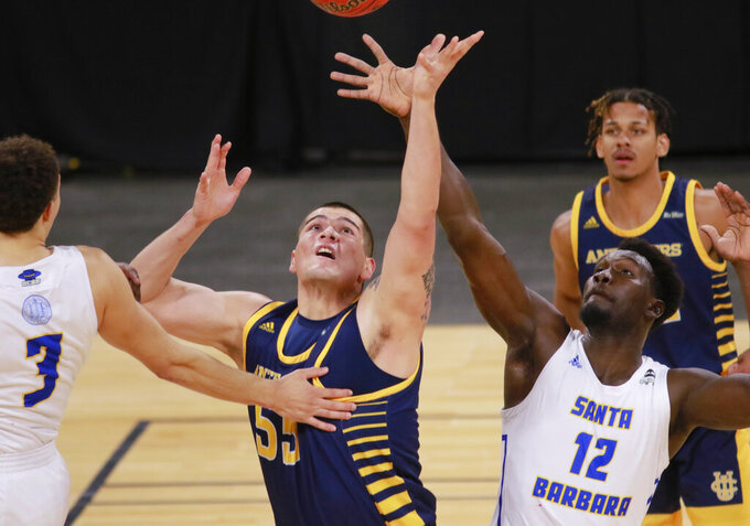 UC Irvine's Brad Greene (55) and UC Santa Barbara's Amadou Sow (12) go for a rebound during the first half of an NCAA college basketball game for the championship of the Big West Conference men's tournament Saturday, March 13, 2021, in Las Vegas. (AP Photo/Ronda Churchill)