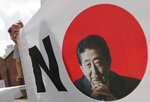 A South Korean man stands next to a sign with a picture of the Japanese Prime Minister Shinzo Abe during a rally to denounce Japan's trade restrictions on South Korea in Seoul, South Korea, Thursday, Aug. 8, 2019. (AP Photo/Lee Jin-man)