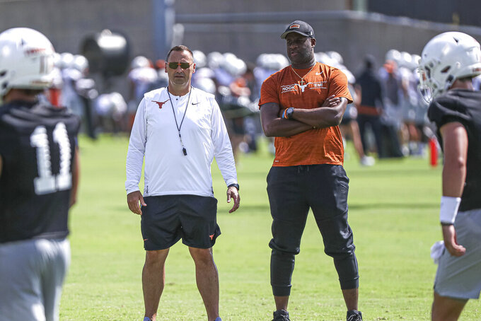Texas coach Steve Sarkisian, left, is joined by former Texas quarterback Vince Young, right, during the NCAA college football team's practice Saturday, Aug. 7, 2021, in Austin, Texas. (Aaron E. Martinez/Austin American-Statesman via AP)