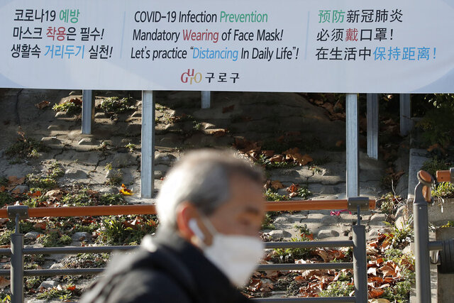 A man wearing a face mask walks past a banner showing precautions against the coronavirus in Seoul, South Korea, Monday, Nov. 23, 2020. (AP Photo/Lee Jin-man)