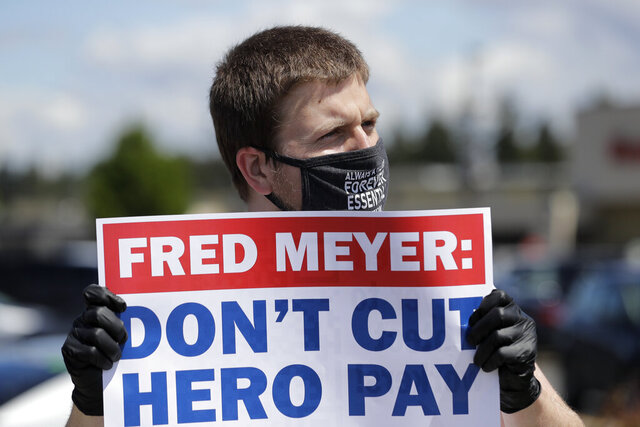 Sherman Jenne, a cashier at the Fred Meyer grocery store in Burien, Wash., takes part in a protest outside the store against Fred Meyer's parent company Kroger, Friday, May 15, 2020, that was organized by the United Food and Commercial Workers International Union. Kroger officials have said they are ending the additional $2 hourly