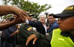 Organization of American States Secretary-General Luis Almagro reaches across a cordon of police to shake hands with a Venezuelan migrant in La Parada, Colombia, border with Venezuela, Friday, Sept. 14, 2018. Almagro traveled to Colombia's border with Venezuela to monitor the situation of migrants who have been fleeing the socialist-run country amid hyperinflation and widespread shortages and widespread shortages. (AP Photo/Fernando Vergara)
