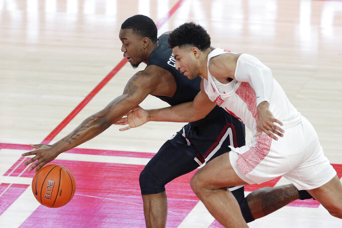 South Carolina guard Jermaine Couisnard, left, reaches a loose ball in front of Houston guard Quentin Grimes, right, during the first half of an NCAA college basketball game Saturday, Dec. 5, 2020, in Houston. (AP Photo/Michael Wyke)
