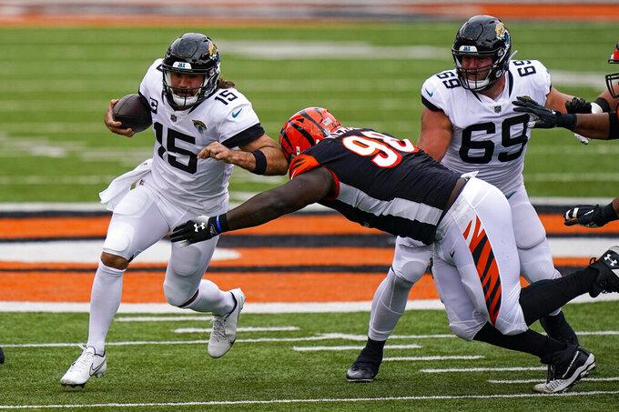Jacksonville Jaguars quarterback Gardner Minshew (15) tries to avoid the tackle of Cincinnati Bengals nose tackle D.J. Reader (98) in the first half of an NFL football game in Cincinnati, Sunday, Oct. 4, 2020. (AP Photo/Bryan Woolston)