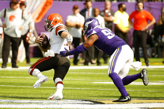 Cleveland Browns quarterback Baker Mayfield runs from Minnesota Vikings defensive end Everson Griffen, right, during the second half of an NFL football game, Sunday, Oct. 3, 2021, in Minneapolis. (AP Photo/Bruce Kluckhohn)