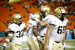 Teammates celebrate after Army running back Sandon McCoy (3), center, made a touchdown against Hawaii during the first half of an NCAA college football game Saturday, Nov. 30, 2019 in Honolulu. (AP Photo/Marco Garcia)