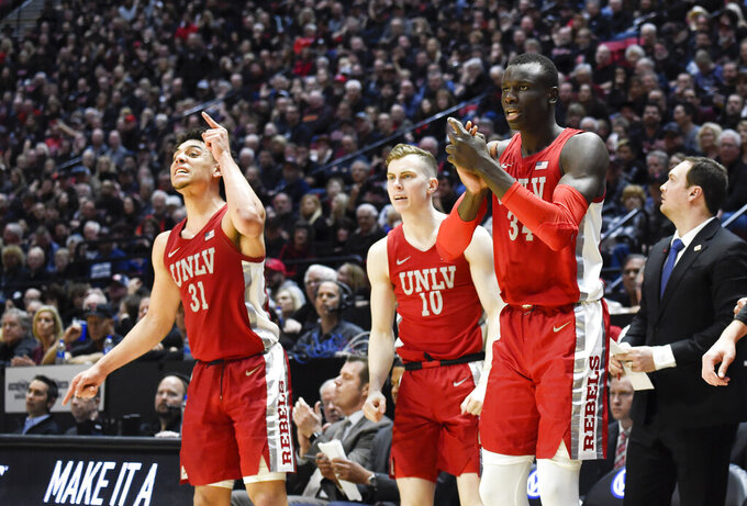 UNLV guard Marvin Coleman (31), Jonah Antonio (10) and Cheikh Mbacke Diong (34) cheer from the bench during the second half of an NCAA college basketball game against San Diego State, Saturday, Feb. 22, 2020, in San Diego. (AP Photo/Denis Poroy)