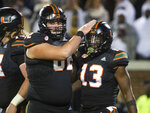 Miami running back DeeJay Dallas (13) is congratulated by offensive lineman Tyler Gauthier after scoring a touchdown during the first half of an NCAA college football game against Georgia Tech on Saturday, Nov. 10, 2018, in Atlanta. (AP Photo/John Amis)