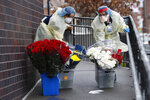 Emergency room nurses transport buckets of donated flowers up a ramp outside Elmhurst Hospital Center's emergency room, Saturday, March 28, 2020, in New York. The hospital has been heavily taxed by treating an influx of coronavirus patients during the current viral pandemic. Currently, New York leads the nation in the number of cases, according to Johns Hopkins University, which is keeping a running tally. (AP Photo/Kathy Willens)