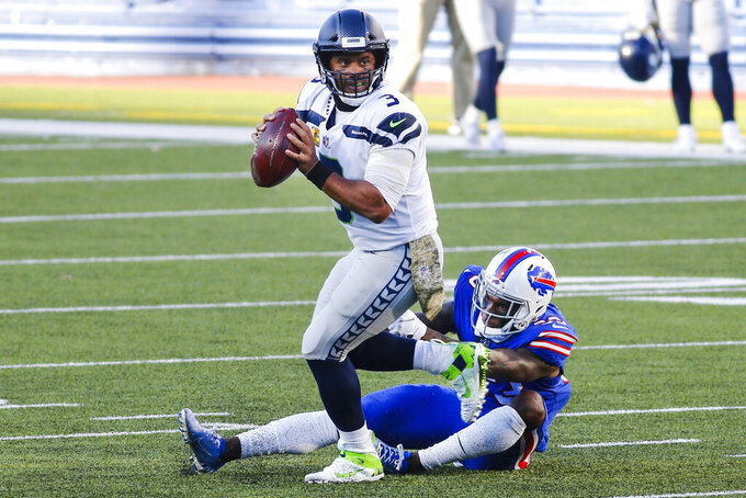 Seattle Seahawks quarterback Russell Wilson, left, evades a sack by Buffalo Bills' Siran Neal during the second half of an NFL football game Sunday, Nov. 8, 2020, in Orchard Park, N.Y. (AP Photo/Jeffrey T. Barnes)