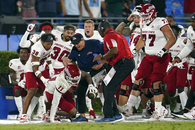 Fresno State wide receiver Josh Kelly (11) celebrates with coaches and teammates after making a catch during the second half of an NCAA college football game against UCLA Sunday, Sept. 19, 2021, in Pasadena, Calif. (AP Photo/Marcio Jose Sanchez)