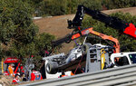 The car of AlphaTauri driver Pierre Gasly of France is lifted by a tow truck during the second practice session prior to the Formula One Portuguese Grand Prix at the Algarve International Circuit in Portimao, Portugal, Friday, Oct. 23, 2020. The Formula One Portuguese Grand Prix will take place on Sunday. (AP Photo/Armando Franca, Pool)