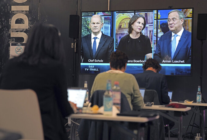 Olaf Scholz, candidate for chancellor of the SPD and Federal Minister of Finance, left, Annalena Baerbock, German Green Party co-leader and candidate for chancellor, center, and Armin Laschet, candidate for chancellor of the CDU/CSU and chairman of the CDU, right, during the start of the third TV debate in Berlin, Sunday Sept. 19, 2021. (Kay Nietfeld/dpa via AP)