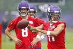 Minnesota Vikings quarterback Kellen Mond (11) throws a pass in front of quarterback Kirk Cousins (8) during NFL football training camp Friday, July 30, 2021, in Eagan, Minn. (AP Photo/Bruce Kluckhohn)
