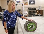 Heather Oravec, research associate professor stationed at the NASA Glenn Research Center, rolls a Nickel Titanium Shape Memory Alloy tire on a simulated off world surface in the Simulated Lunar Operations Lab in Cleveland on Sept. ,9, 2019. The material in the tire can deform but returns to its original shape. Oravec's research in extraterrestrial soil mechanics and extraterrestrial surface mobility helps in developing new tires for off world vehicles and rovers. (Mike Cardew/Akron Beacon Journal via AP)