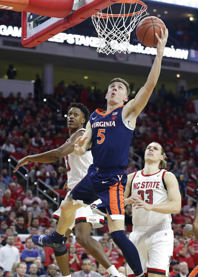 Virginia's Kyle Guy (5) drives to the basket while North Carolina State's C.J. Bryce and Wyatt Walker (33) defend during the second half of an NCAA college basketball game in Raleigh, N.C., Tuesday, Jan. 29, 2019. Virginia won 66-65 in overtime. (AP Photo/Gerry Broome)