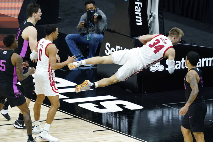 Wisconsin's Brad Davison (34) calls timeout after diving for a loose ball during the second half of an NCAA college basketball game against Penn State at the Big Ten Conference tournament, Thursday, March 11, 2021, in Indianapolis. Wisconsin won 75-74. (AP Photo/Darron Cummings)