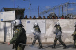 Greek Riot Police walk outside Moria camp, as refugees and migrants protest following the stabbing death of an 20-year-old man from Yemen in the Greek island of Lesbos, Friday, Jan, 17, 2020. Authorities arrested a 27-year-old Afghan migrant in connection with the incident. Overcrowding at Moria has steadily worsened over the past year as the number of arrivals of migrants and refugees using clandestine routes from Turkey to the Greek islands remains high _ and totaled nearly 60,000 in 2019. (AP Photo/Aggelos Barai)