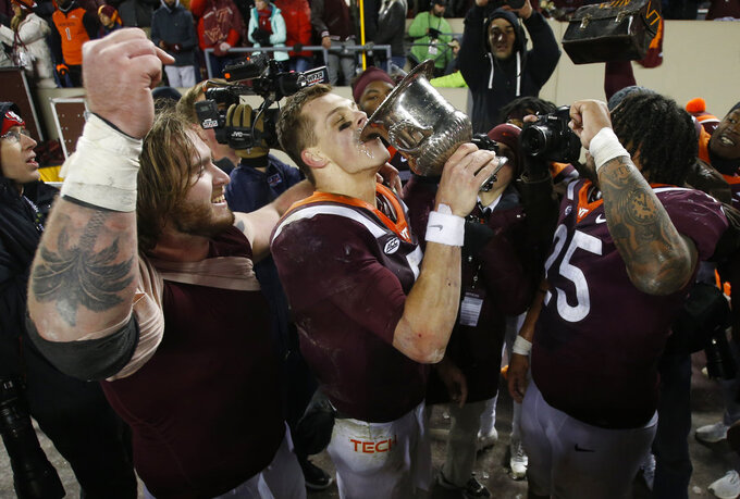 Virginia Tech quarterback Ryan Willis, center, drinks from the Commonwealth Cup after his team defeated Virginia 34-31 in overtime of an NCAA college football game in Blacksburg, Va., Friday, Nov. 23, 2018. (AP Photo/Steve Helber)