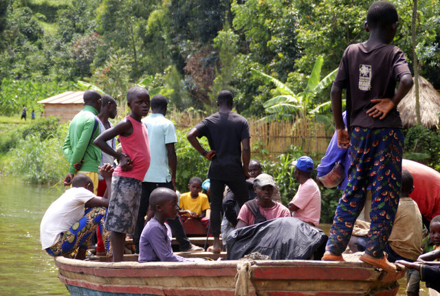 Children gather around a wooden boat conveying two bodies, in Mukwija in Eastern Congo, Wednesday Jan. 6, 2021. Authorities in eastern Congo fear more than 40 people are dead after a motorized wooden boat capsized on Lake Kivu overnight, officials said Wednesday. (AP Photo/Justin Kabumba)