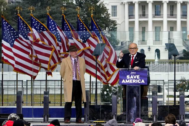 FILE - In this Jan. 6, 2021, file photo, Chapman University law professor John Eastman stands at left as former New York Mayor Rudolph Giuliani speaks in Washington at a rally in support of President Donald Trump, called the