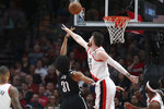 Brooklyn Nets center Jarrett Allen shoots next to Portland Trail Blazers center Jusuf Nurkic during the first half of an NBA basketball game in Portland, Ore., Monday, March 25, 2019. (AP Photo/Randy L. Rasmussen)