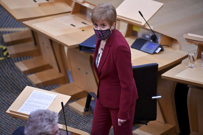 Scotland's First Minister Nicola Sturgeon looks on during First Minister's Questions at the Scottish Parliament in Edinburgh, Thursday, Nov. 19, 2020. (Jeff J Mitchell/PA via AP)