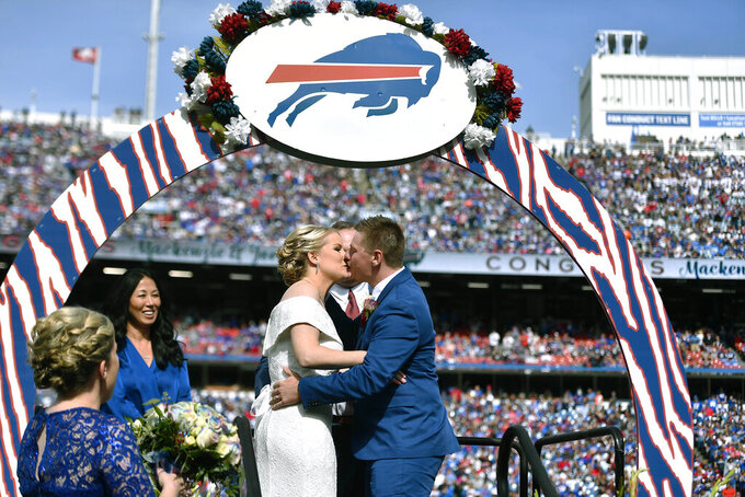 Mackenzie Park and Jordan Binggeli share a kiss after being married during a wedding ceremony at midfield during halftime of an NFL football game between the Buffalo Bills and the New England Patriots, Sunday, Sept. 29, 2019, in Orchard Park, N.Y. (AP Photo/Adrian Kraus)