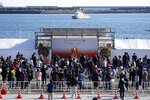 Visitors queue to see the Olympic Flame during a flame display ceremony in Iwaki, Fukushima Prefecture, northern Japan, Wednesday, March 25, 2020. IOC President Thomas Bach has agreed