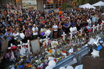 FILE - In this Aug. 6, 2019, file photo, people crowd around a makeshift memorial at the scene of a mass shooting at a shopping complex in El Paso, Texas. In the days and weeks since three high-profile shootings took the lives of more than two dozen people in just a week's time, law enforcement authorities have reported seeing a spike in the number of tips they are receiving from concerned relatives, friends and co-workers of people who appear bent on carrying out the next mass shooting. (AP Photo/John Locher, File)