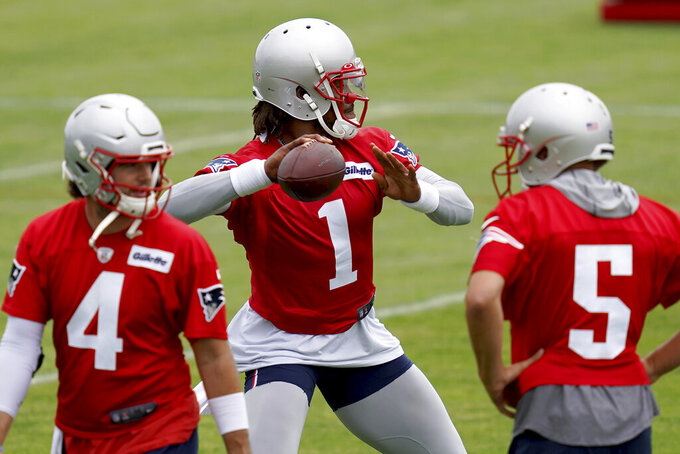 New England Patriots quarterback Cam Newton throws a pass as Jarrett Stidham (4) and Brian Hoyter (5) look on during NFL football practice in Foxborough, Mass., Friday, June 4, 2021. (AP Photo/Mary Schwalm)