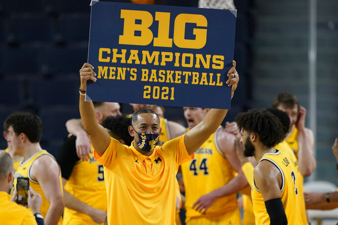 Michigan coach Juwan Howard holds a championship sign after after the team's win over Michigan State in an NCAA college basketball game Thursday, March 4, 2021, in Ann Arbor, Mich. (AP Photo/Carlos Osorio)