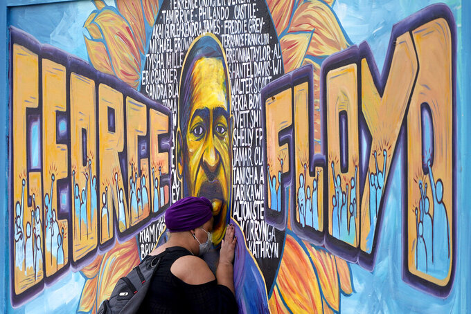 FILE - In this April 23, 2021, file photo, Damarra Atkins pays her respects to George Floyd at a mural at George Floyd Square, in Minneapolis. A fund set up to honor George Floyd says it has awarded more than $50,000 in scholarships since it was created. The George Floyd Memorial Foundation says Monday, Sept. 13, 2021, that it has recently given scholarships to 15 law school students, (AP Photo/Julio Cortez, File)