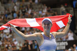 Denmark's Caroline Wozniacki unfurls Denmark's flag after her third round loss to Tunisia's Ons Jabeur at the Australian Open tennis championship in Melbourne, Australia, Friday, Jan. 24, 2020. (AP Photo/Andy Brownbill)