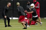 Arizona Cardinals quarterback Kyler Murray (1) tosses the ball to a coach as head coach Kliff Kingsbury, left, looks on as the quarterbacks run drills during an NFL football workout Wednesday, Aug. 12, 2020, in Glendale, Ariz. (AP Photo/Ross D. Franklin)