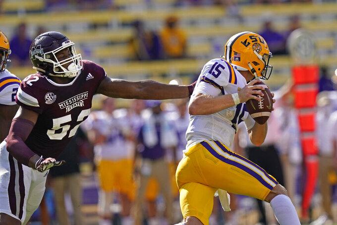LSU quarterback Myles Brennan (15) scrambles under pressure from Mississippi State defensive end Kobe Jones (52) in the first half an NCAA college football game in Baton Rouge, La., Saturday, Sept. 26, 2020. (AP Photo/Gerald Herbert)
