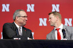 In this Dec. 3, 2017, file photo, Newly hired Nebraska head NCAA college football coach Scott Frost, right, shakes the hand of athletic director Bill Moos during a news conference in Lincoln, Neb. Nebraska's 68-year-old athletic director has pulled off two of the splashiest hires in college athletics in the 18 months since he arrived. He brought Frost back to his alma mater after he coached Central Florida to an unbeaten season in 2017. This week he hired former Iowa State star player and coach Fred Hoiberg. (AP Photo/Nati Harnik, File)