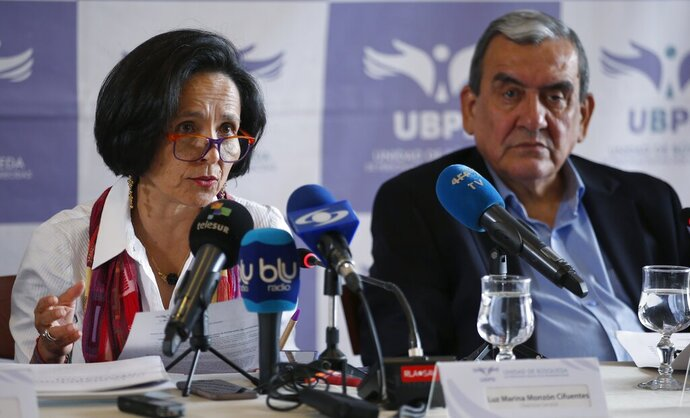 Luz Marina Monzon, director of the missing person's unit, left, and Jaime Alberto Parra, an ex-combatant of the Revolutionary Armed Forces of Colombia, FARC, take part in a presentation on information on those disappeared during the nation's civil conflict, in Bogota, Colombia, Tuesday, Aug. 20, 2019. A special unit tasked by Colombia's peace process to search for the thousands who disappeared over more than five decades of conflict will analyze the information and work with authorities to try and locate remains. (AP Photo/Fernando Vergara)