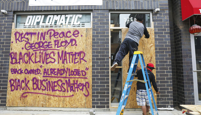 Diplomatic 1750, a sneaker and streetwear consignment boutique owned by Brian Heath, is boarded up in Chicago on June 1, 2020. Heath, who is black, said he's upset that his sneaker and streetwear consignment boutique in Chicago's Wicker Park neighborhood was vandalized on Sunday. But he's even more upset about Floyd's death, which triggered the unrest. (AP Photo/Teresa Crawford)