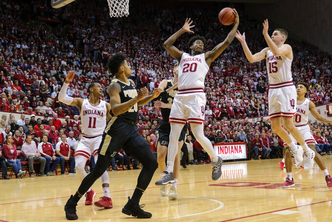 Indiana forward De'Ron Davis (20) pulls down a rebound in front of teammate Zach McRoberts (15) and Purdue guard Nojel Eastern (20) during the first half of an NCAA college basketball game in Bloomington, Ind., Tuesday, Feb. 19, 2019. (AP Photo/AJ Mast)
