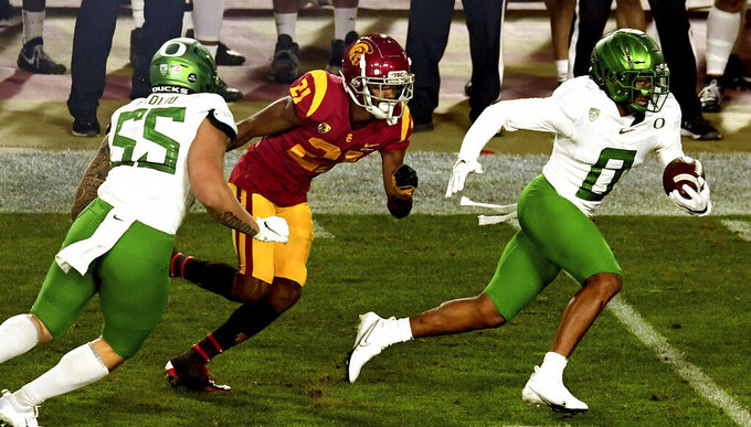 Cornerback Deommodore Lenoir, right, of Oregon, intercepts a pass intended for wide receiver Tyler Vaughns, center, of USC in the first half of an NCAA college football game at the Los Angeles Memorial Coliseum in Los Angeles on Friday, Dec. 18, 2020. (Keith Birmingham/The Orange County Register via AP)