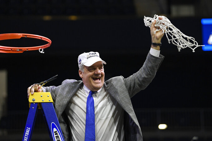 Hofstra coach Joe Mihalich holds up the net after cutting it down following the team's win over Northeastern in an NCAA college basketball game for the Colonial Athletic Association men's tournament title Tuesday, March 10, 2020, in Washington. Hofstra won 70-61. (AP Photo/Nick Wass)