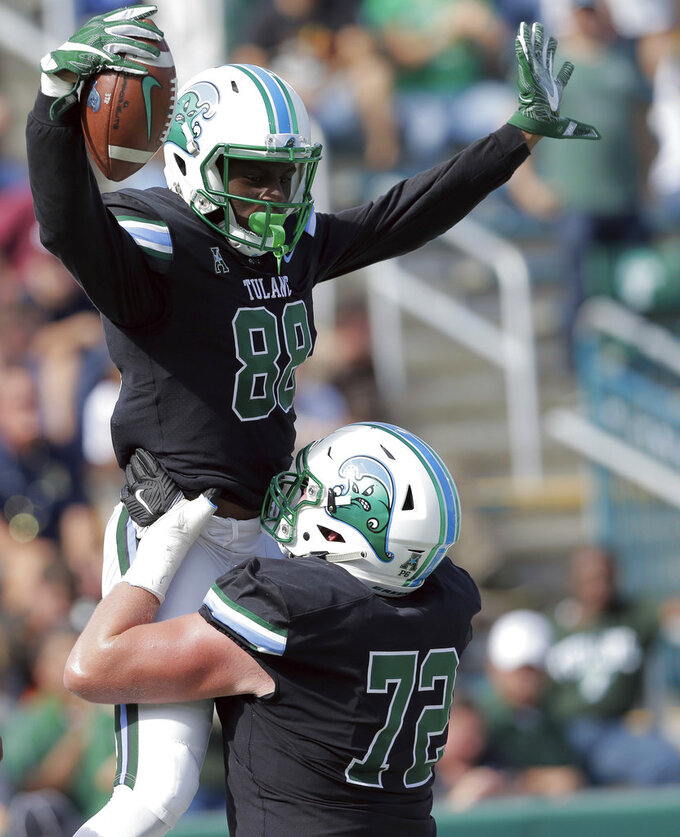 Tulane wide receiver Jabril Clewis (88) celebrates scoring a touchdown with offensive lineman John Leglue (72) during an NCAA college football game against Navy at Yulman Stadium in New Orleans, Saturday, Nov. 24, 2018. (David Grunfeld/The Times-Picayune via AP)