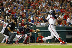Atlanta Braves' Nick Markakis hits a sacrifice fly ball in front of Washington Nationals catcher Yan Gomes and umpire Rob Drake in the fifth inning of a baseball game against the Washington Nationals, Friday, Sept. 13, 2019, in Washington. Ronald Acuña Jr. scored on the play. (AP Photo/Patrick Semansky)