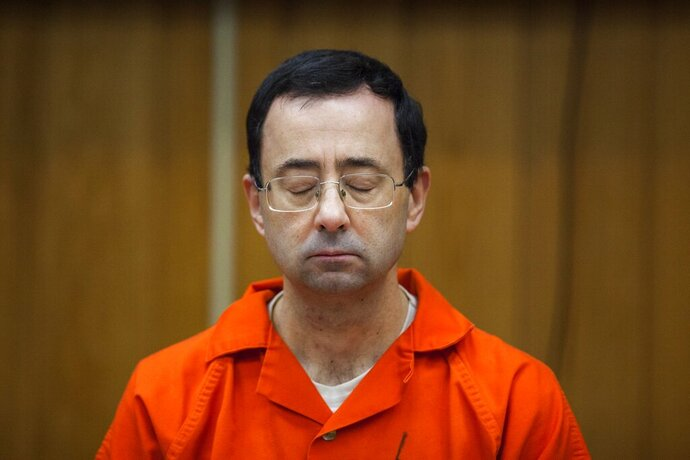 """FILE - In this Feb. 5, 2018, file photo, Larry Nassar listens during his sentencing at Eaton County Circuit Court in Charlotte, Mich.  Michigan's attorney general on Wednesday, Dec. 25, 2019,  described as """"inadvertently misleading"""" a statement from her communications director this week that her office has suspended a nearly two-year-long criminal investigation into Michigan State University's handling of complaints against the now-imprisoned serial sexual abuser.   Attorney General Dana Nessel said in a written statement Wednesday that the investigation was ongoing.  (Cory Morse/The Grand Rapids Press via AP, File)"""