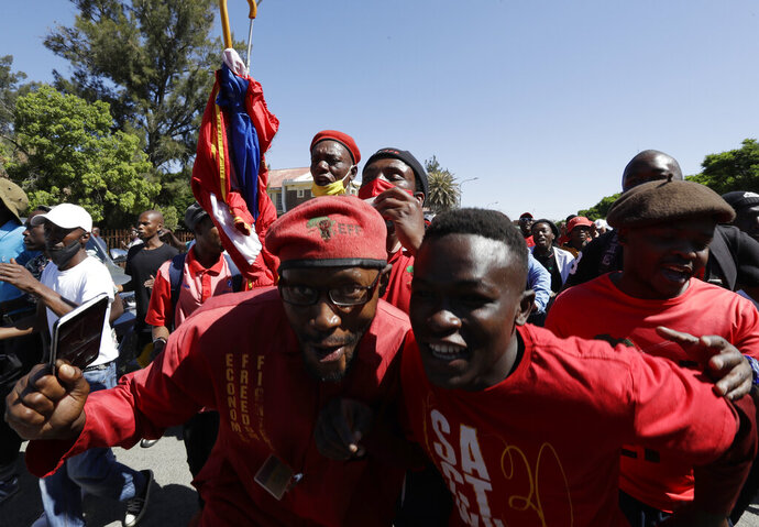 Members of the Economic Freedom Fighters protest outside the magistrates court in Senekal, South Africa, Friday, Oct. 16, 2020, where two suspects were to appear on charges of killing a white farmer in the area. (AP Photo/Themba Hadebe)