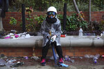 A protester rests at Hong Kong Polytechnic University after police stormed part of the campus during the early morning hours in Hong Kong, Monday, Nov. 18, 2019. Police breached the university campus held by protesters early Monday after an all-night siege that included firing repeated barrages of tear gas and water cannons. (AP Photo/Vincent Yu)