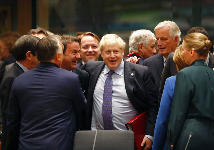 British Prime Minister Boris Johnson, center, is greeted by Luxembourg's Prime Minister Xavier Bettel, center left, during a round table meeting at an EU summit in Brussels, Thursday, Oct. 17, 2019. Britain and the European Union reached a new tentative Brexit deal on Thursday, hoping to finally escape the acrimony, divisions and frustration of their three-year divorce battle. (AP Photo/Frank Augstein)