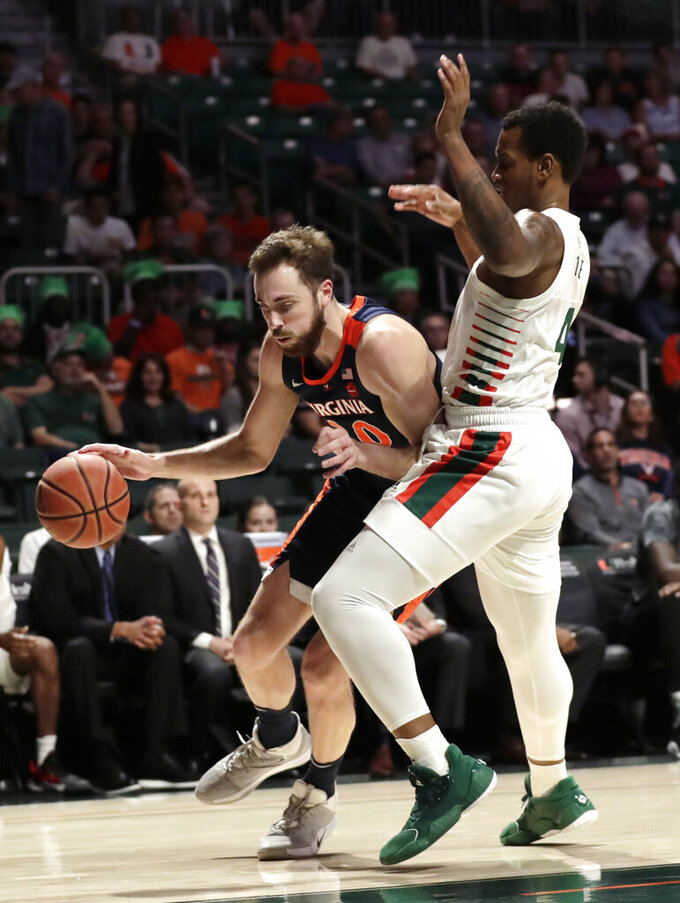 Virginia forward Jay Huff, left, drives to the basket as Miami forward Keith Stone (4) defends during the first half of an NCAA college basketball game, Wednesday, March 4, 2020, in Coral Gables, Fla. (AP Photo/Lynne Sladky)
