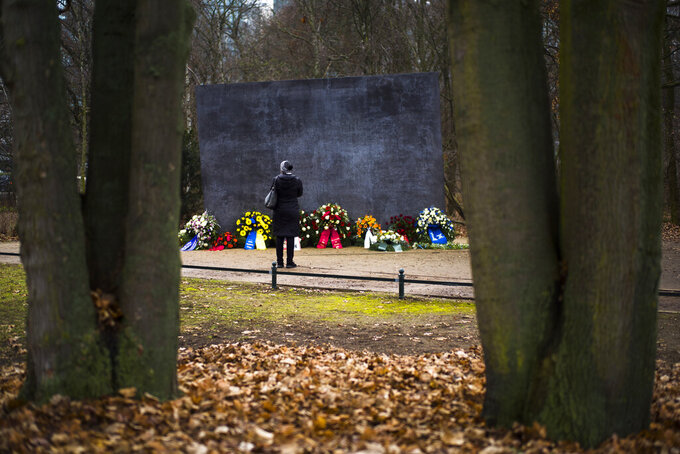 A woman stand in front of the Memorial to Homosexuals, persecuted under Nazism, in Berlin, Germany, Wednesday, Jan. 27, 2021 during the International Holocaust Remembrance Day. (AP Photo/Markus Schreiber)